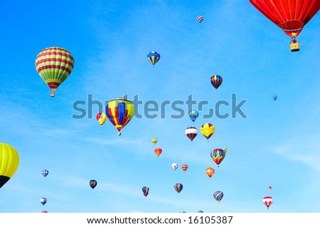Multicoloured balloon flying in the clean blue sky