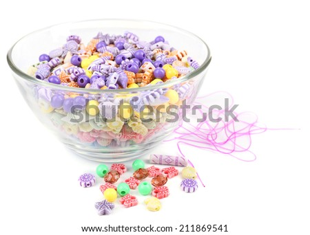 Multicoloured beads in glass bowl isolated on white