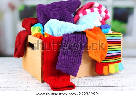 Multicoloured socks in a box on a wooden table in front of the window - stock photo