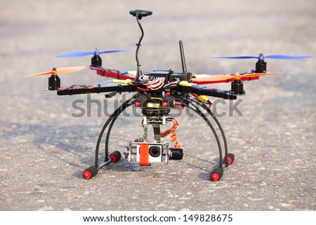 Multicopter with camera in brushless gimbal and autopilot ready for take-off - stock photo