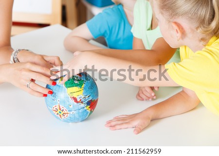 Multicultural children hands on a globe - stock photo