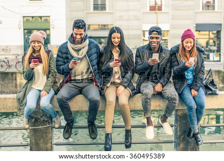 Multicultural group of friends using cellphones - Students sitting in a row and typing on the smartphones - stock photo