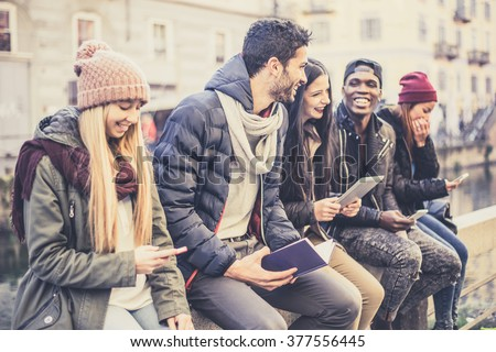 Multicultural group of friends using cellphones - Students sitting in a row and typing on the smartphones, vintage filtered look - stock photo