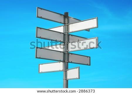 Multidirectional blank metal signpost over blue sky - stock photo