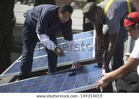 Multietchinc engineers placing solar panel together on rooftop - stock photo