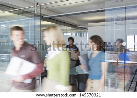 Multiethnic blurred office workers leaving conference room - stock photo
