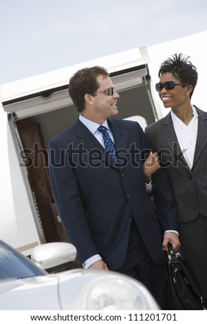 Multiethnic business couple standing together with airplane in the background at airfield - stock photo