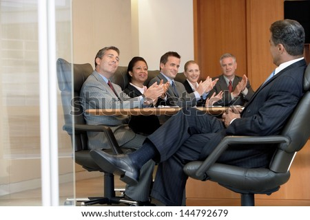 Multiethnic business people applauding boss in office meeting - stock photo