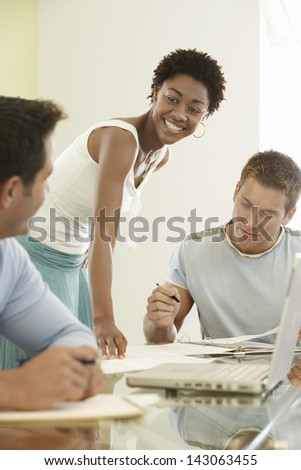 Multiethnic business people busy with paperwork at conference table - stock photo