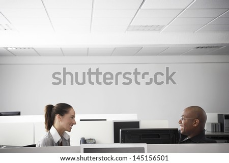 Multiethnic business people having casual meeting in office cubicle - stock photo