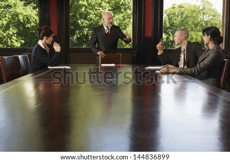 Multiethnic business people having discussion around boardroom table - stock photo