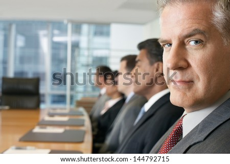 Multiethnic business people sitting in row at conference meeting - stock photo