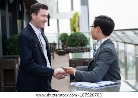 Multiethnic businessmen shaking hands - stock photo