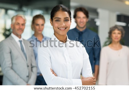 Multiethnic businesswoman standing with her colleagues in background. Portrait of happy smiling business woman looking at camera with team behind. Successful young woman with arms crossed posing. - stock photo