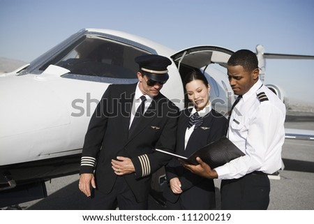 Multiethnic cabin crew members discussing reports together with airplane in the background at airfield - stock photo