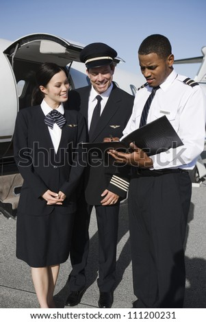 Multiethnic Cabin crew members discussing reports with airplane in the background at airfield - stock photo