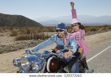 Multiethnic couple having fun on bike ride - stock photo