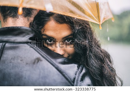 Multiethnic couple of lovers hugging under the umbrella on a rainy day -  Man and woman on a romantic date under the rain, boyfriend hugs his partner to protect her - stock photo