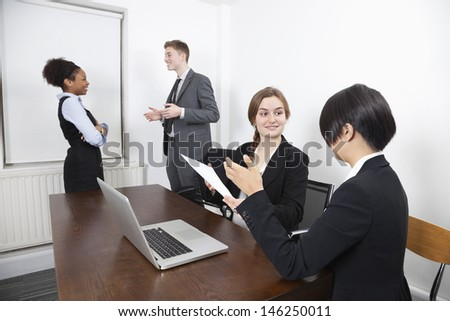 Multiethnic females with document and laptop while colleagues conversing in background