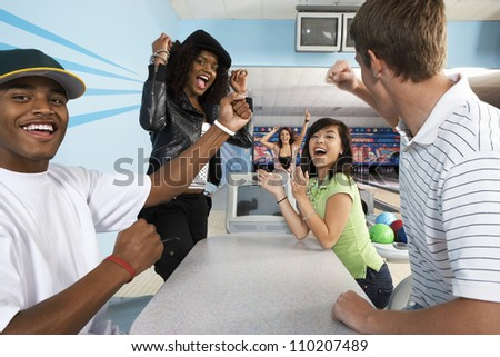 Multiethnic friends cheering at bowling alley - stock photo