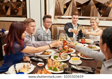 Multiethnic friends clinking with champagne glasses at dinner