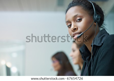 multiethnic group of female customer service representatives talking on the phone, with african woman looking at camera. Horizontal shape, side view, copy space - stock photo