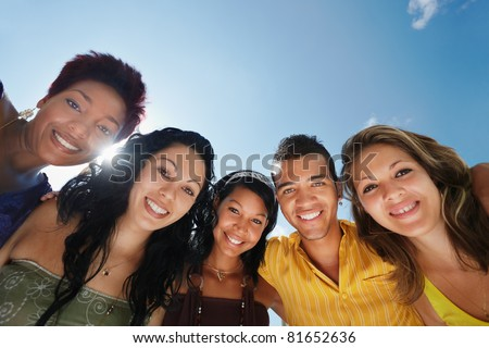 multiethnic group of five male and female friends hugging and looking at camera with sky in background. Low angle view, copy space