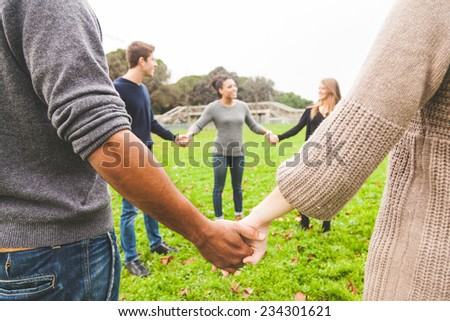 Multiethnic Group of Friends Holding Hands in a Circle - stock photo