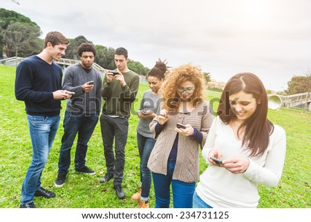 Multiethnic Group of Friends, Smart Phone Addicted. Everyone is looking at his own Phone without caring of other persons around him. - stock photo