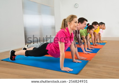 Multiethnic Group Of People Doing Push Ups On Exercise Mat - stock photo