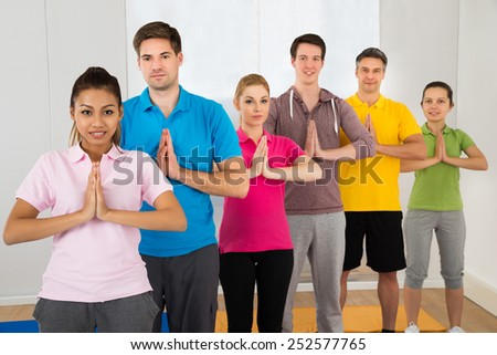 Multiethnic Group Of People Doing Yoga At Fitness Centre - stock photo