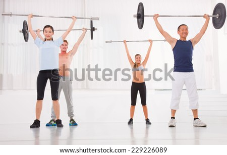 Multiethnic group of people exercising with weightlifting bar in gym - stock photo