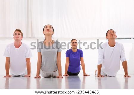 Multiethnic group of people practicing yoga - stock photo