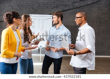 Multiethnic group of smiling young business people standing and talking in conference room - stock photo