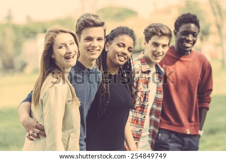 Multiethnic group of teenagers outdoor. They are embraced at park, two boys and one girl are caucasian, one boy and one girl are black. Friendship, immigration, integration and multicultural concepts. - stock photo