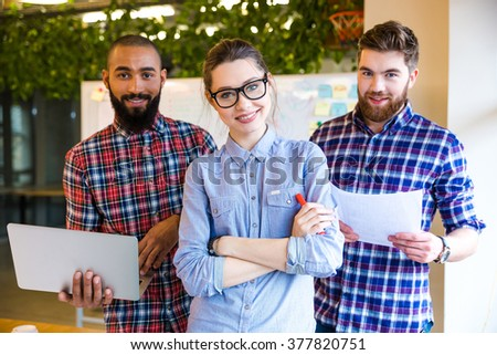Multiethnic group of young business people standing in office and looking at camera - stock photo
