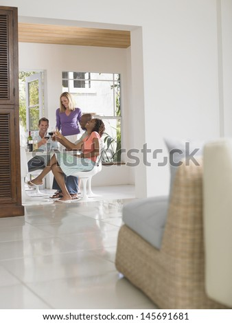 Multiethnic group toasting with wineglasses at home - stock photo