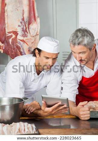 Multiethnic male butchers using tablet computer while leaning on counter in butchery - stock photo
