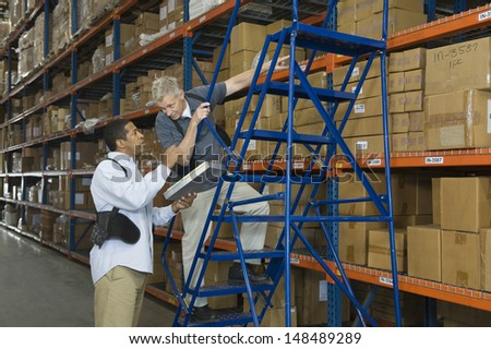 Multiethnic men working in distribution warehouse - stock photo