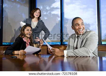 Multiethnic office workers in boardroom watching presentation, laughing, focus on man - stock photo
