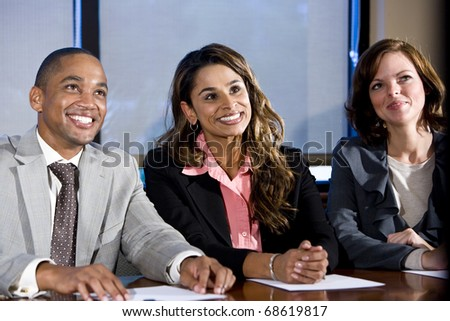 Multiethnic office workers in boardroom watching presentation, main focus on woman in middle - stock photo