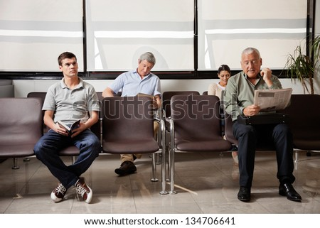 Multiethnic people waiting for the doctor in hospital lobby - stock photo