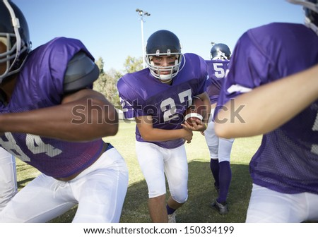 Multiethnic players playing American football on field - stock photo