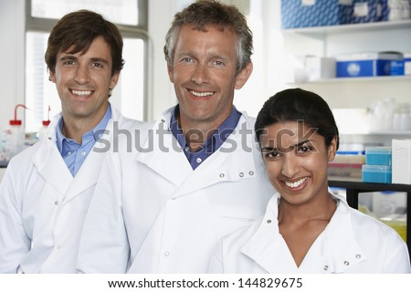 Multiethnic team of scientists smiling in laboratory - stock photo