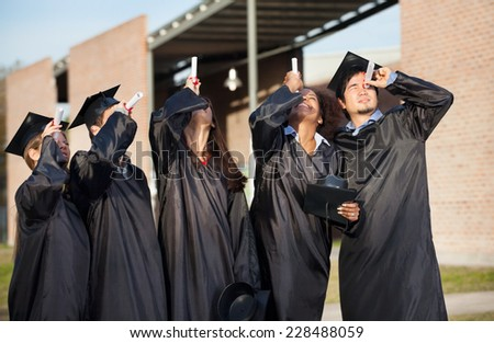 Multiethnic university students in graduation gown looking through certificates on campus - stock photo