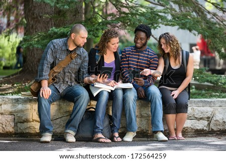 Multiethnic university students using digital tablet while studying on parapet at campus - stock photo