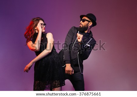 Multiethnic young couple in glasses dancing and having fun over colorful background - stock photo
