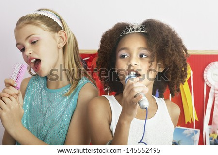 Multiethnic young girls using brushes as microphones to sing at a slumber party - stock photo