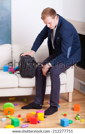 Multifunctional man looking at the mess in his living room - stock photo