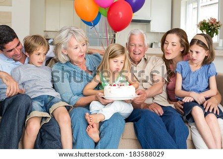 Multigeneration family celebrating girls birthday at home - stock photo